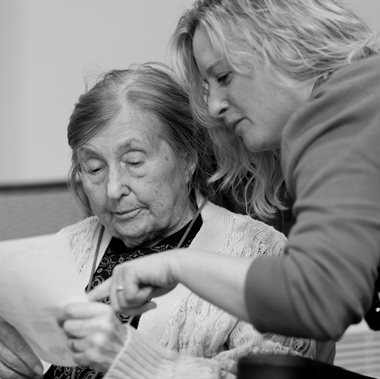 Care worker reading with an individual who needs care and support