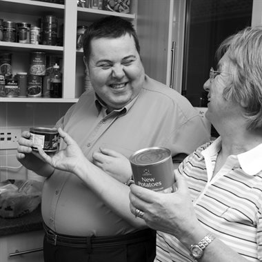 Man in his kitchen smiling at his personal assistant